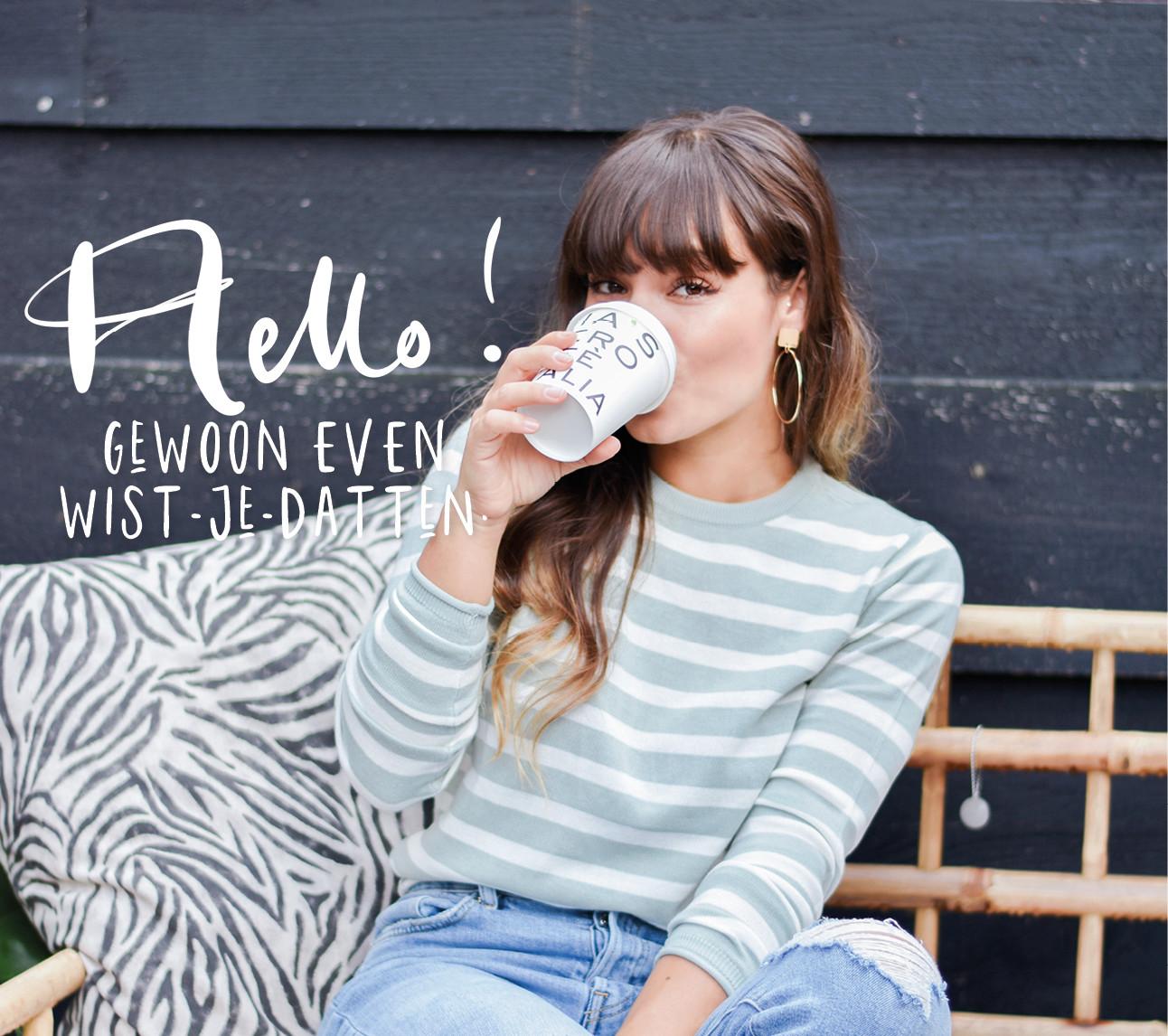 Kiki lachend op een bankje buiten met een kop koffie