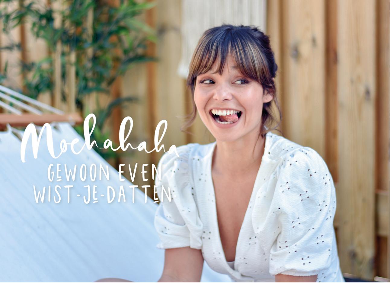 Kiki lachend en haar tong uitsteken in een wit jurkje in de tuin