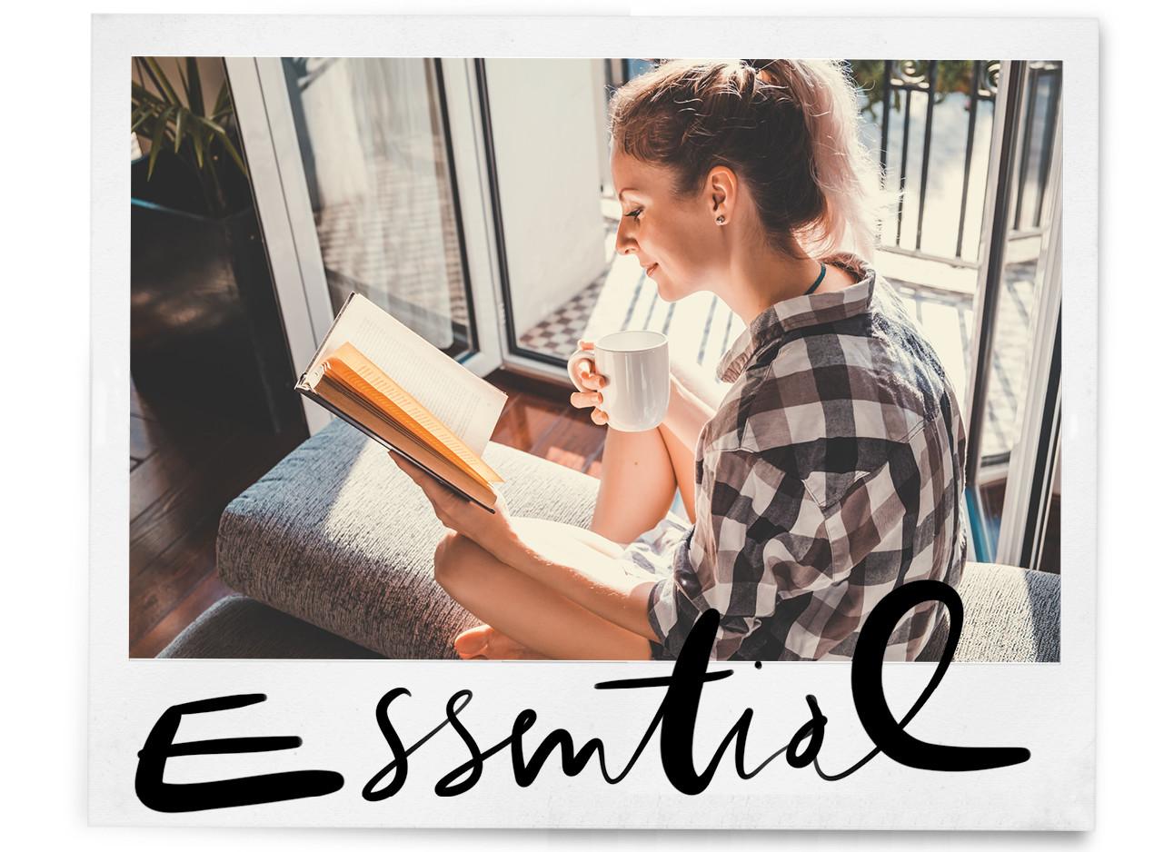 een meisje dta op een bank zit voor het raam ze draagt een ruit blouse en drinkt uit een witte mok, ze leest een boek