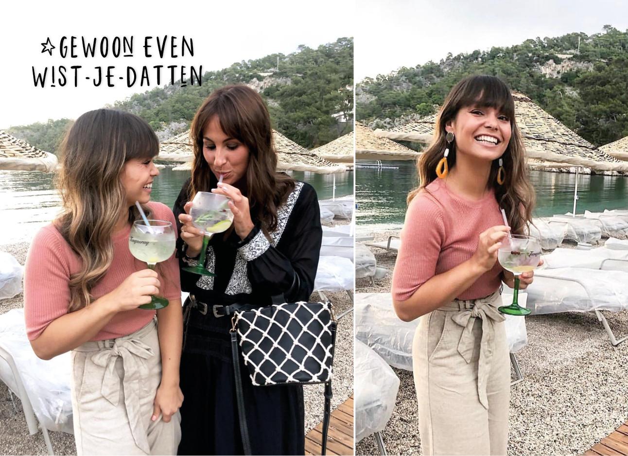 2 vrouwen lachen op het strand met een drankje