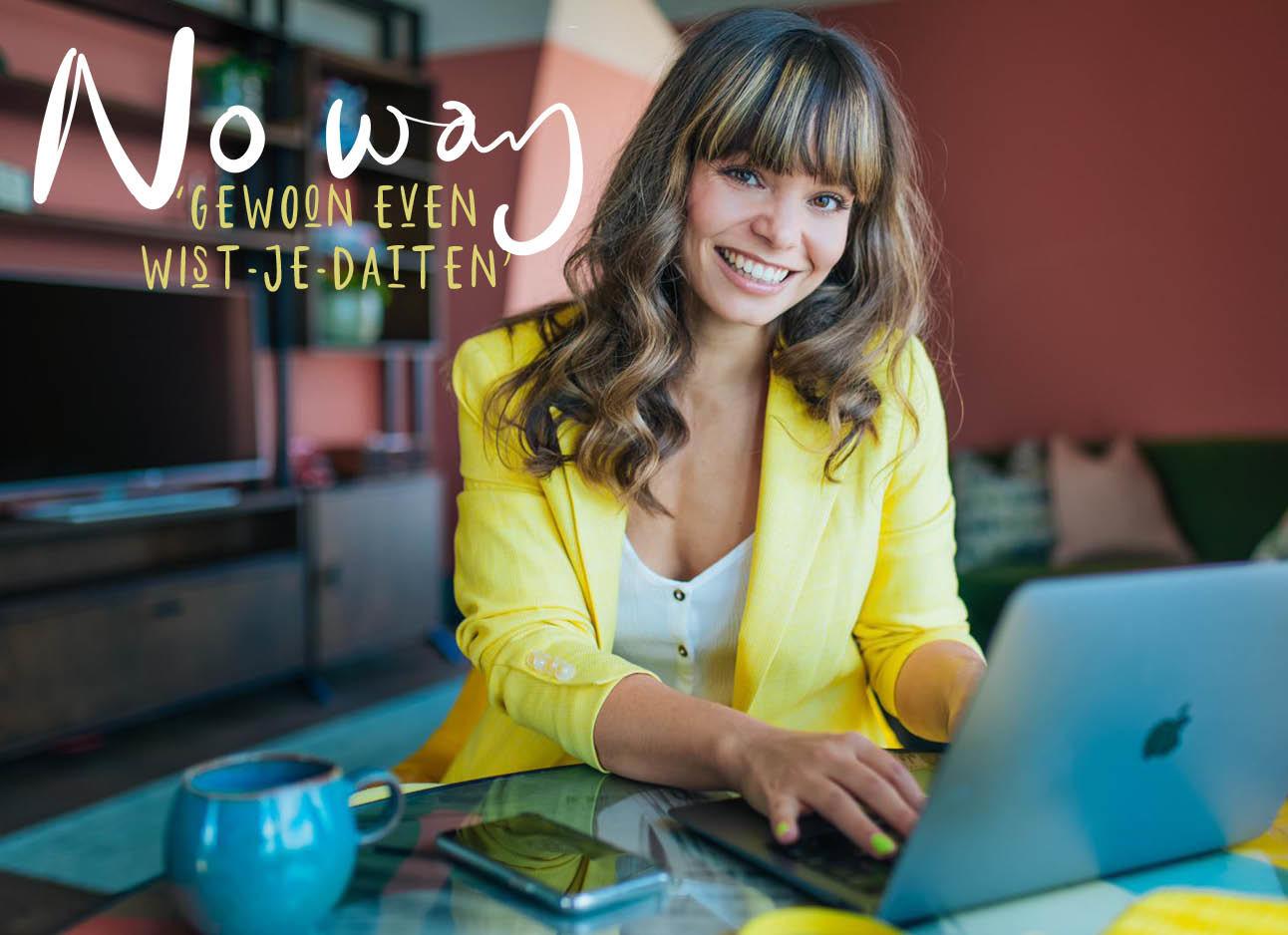 kiki achter haar laptop lachend in een geel jasje