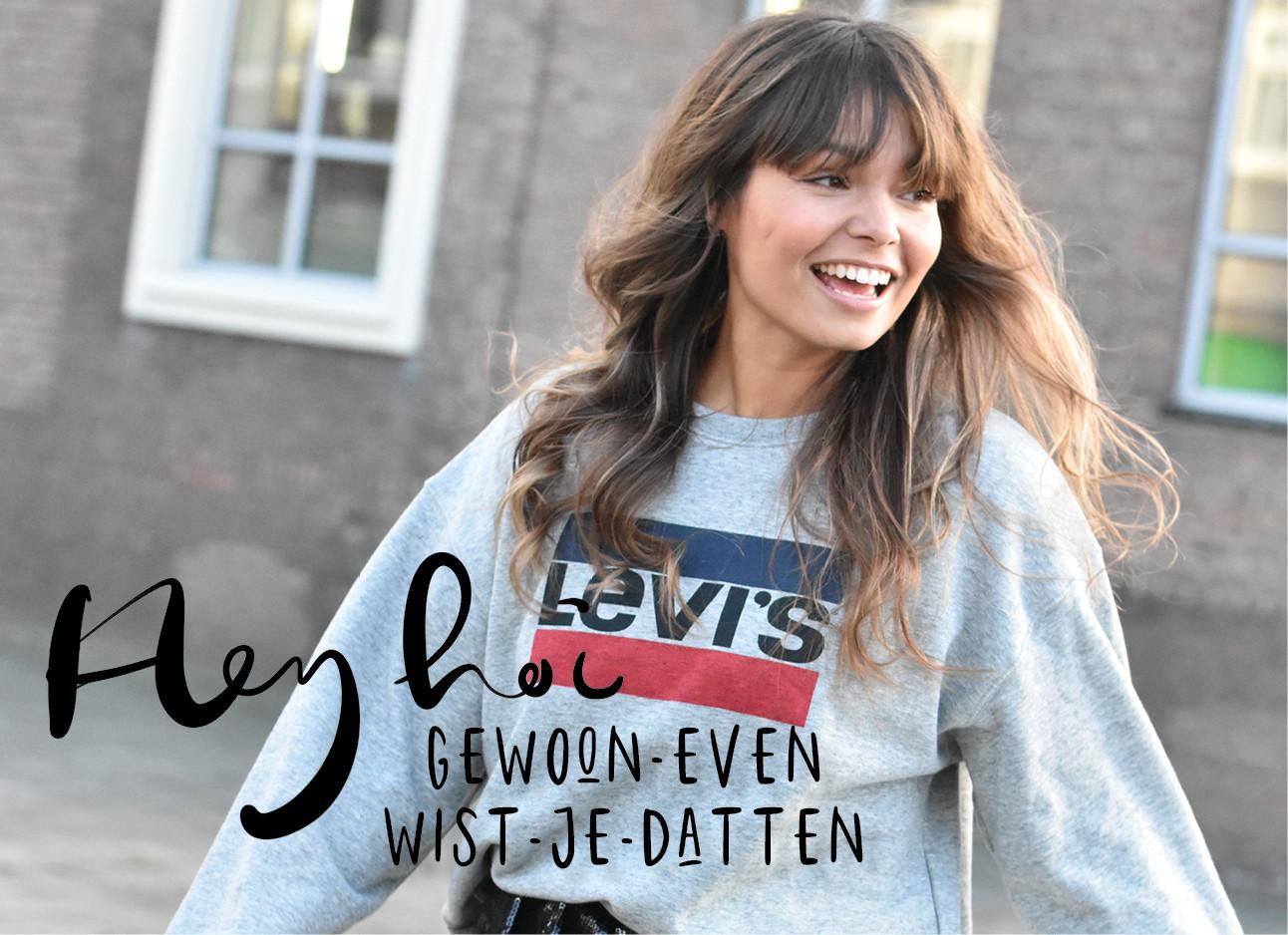 Kiki die lachend op straat lopopt en levi's trui draagt