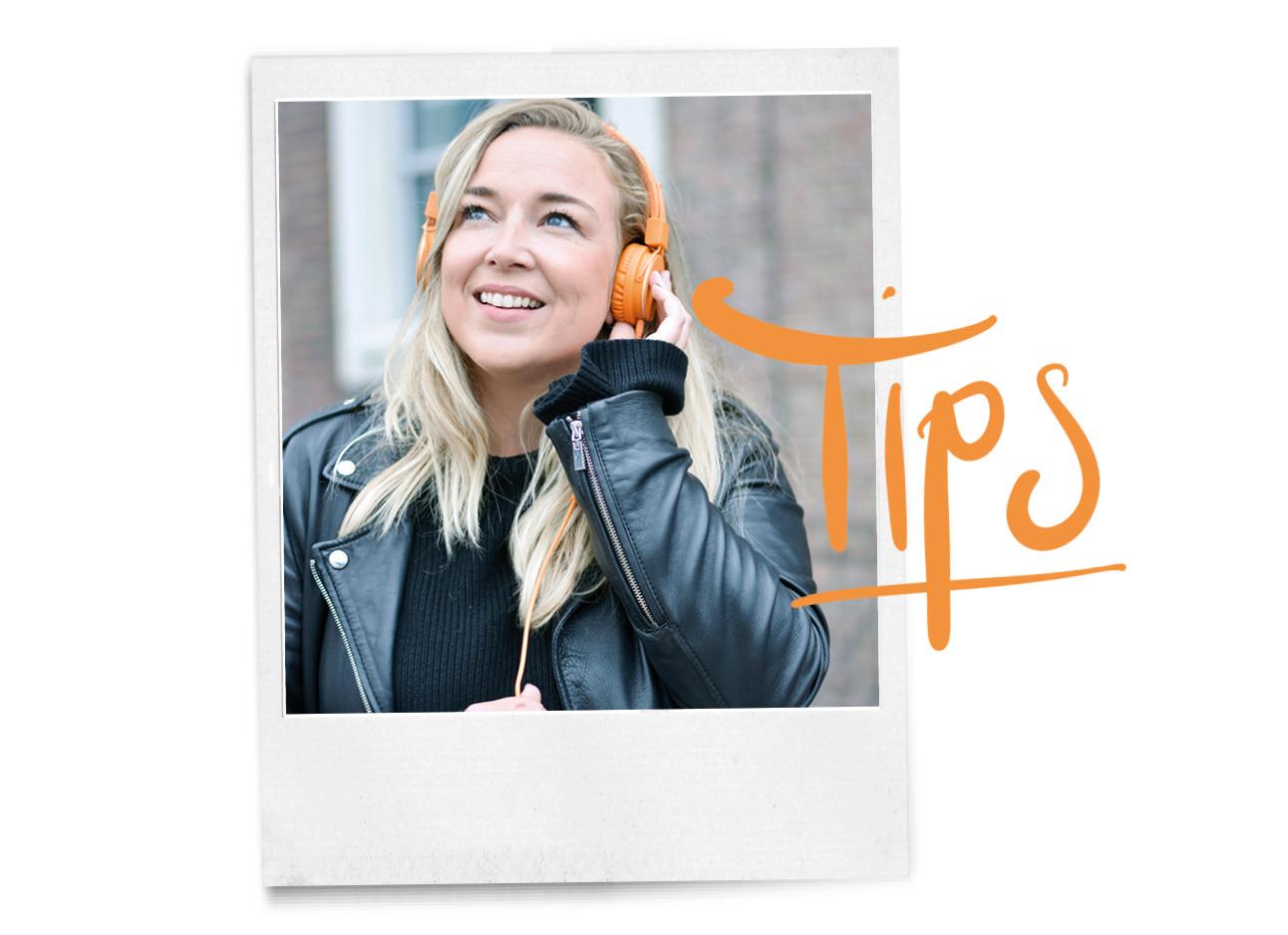Adeline die een leren jasje draagt en een zwarte trui, ze draagt verder nog een oranje koptelefoon