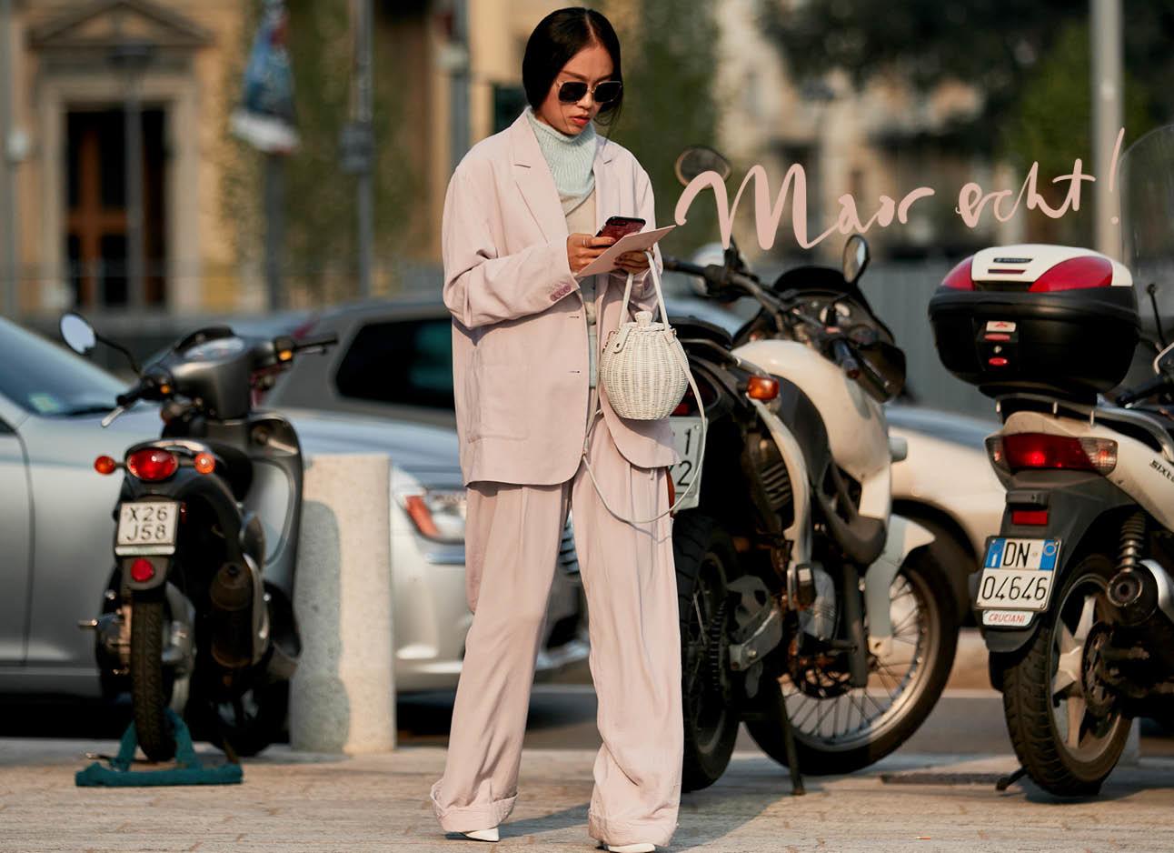 vrouw in roze pak loopt over straat kijkend op haar telefoon