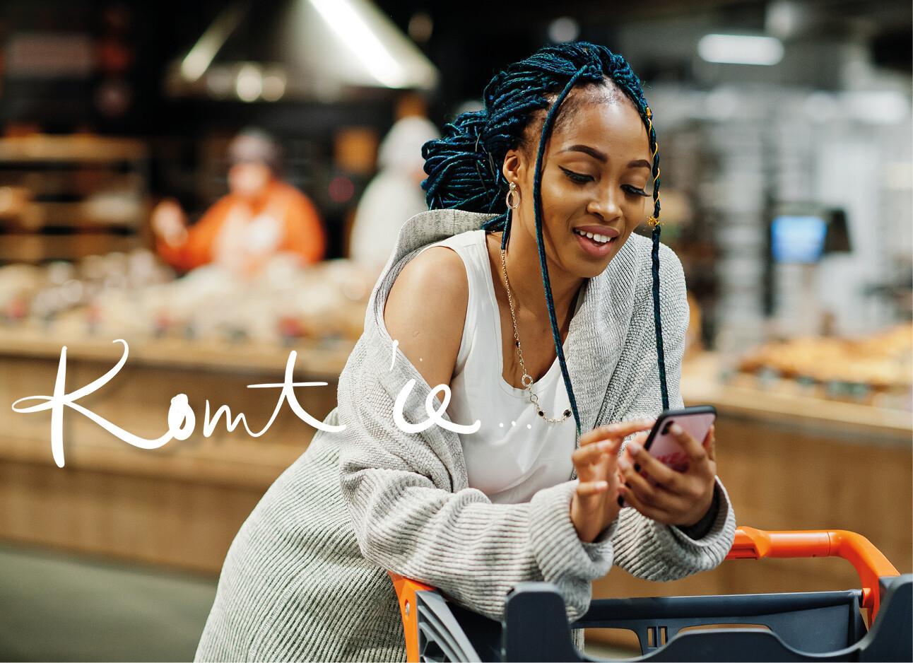 vrouw kijkend op haar telefoon leunend op een winkelwagentje