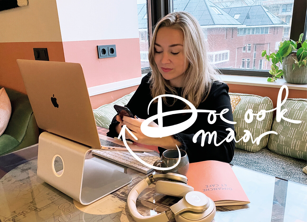 adeline kijkend naar haar telefoon achter haar laptop