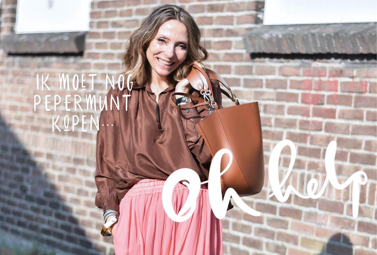 May-britt lachend buiten op straat met Wandler tas en roze rok