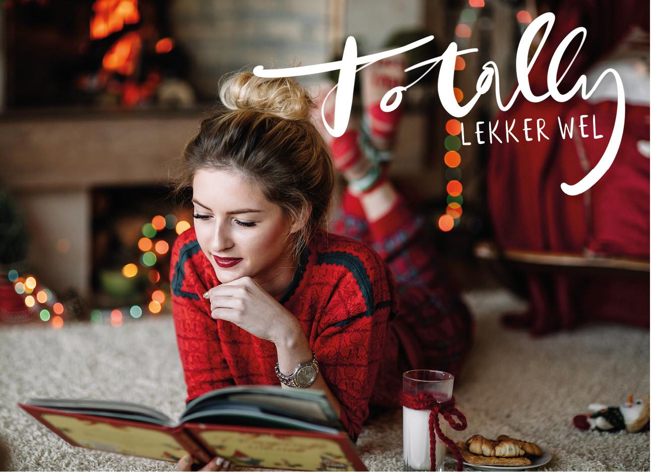een meisje dat in haar pyjama op de grond een boek aan t lezenis