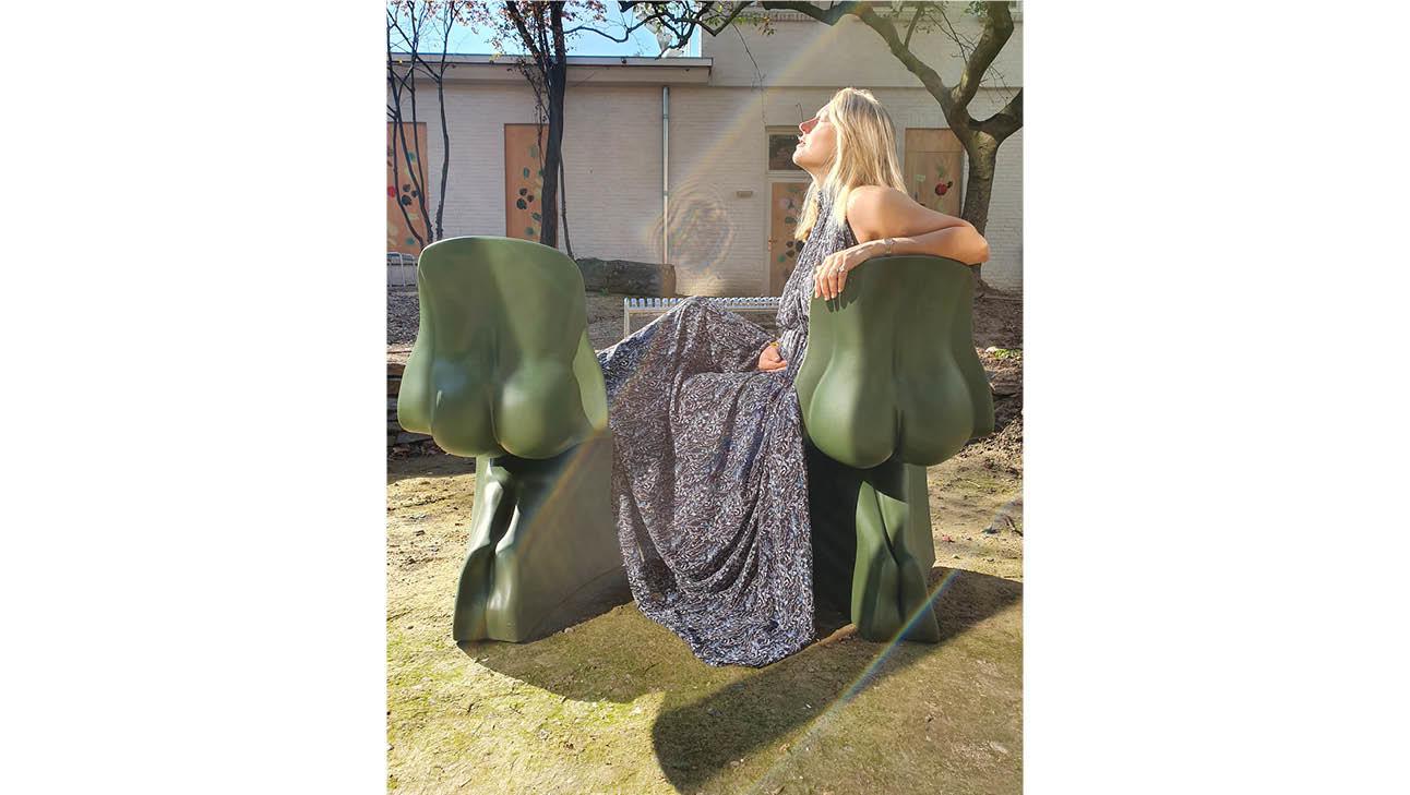 carolien die zit op groene stoelen in een lange grijze jurk