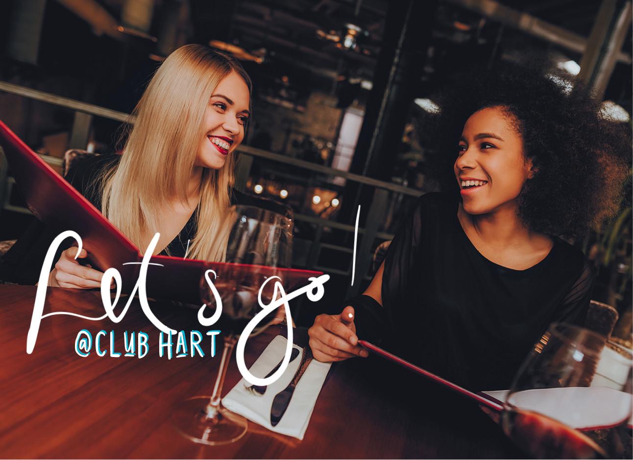 twee vrouwen in een restaurant lachend met een menukaart