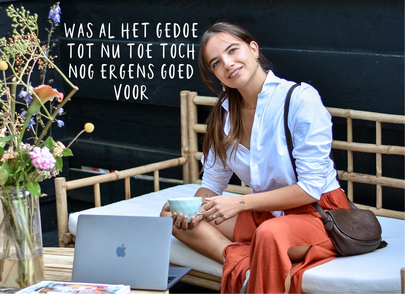 Tess Hoens die op de bank zit en een rode rok draagt met een witte blouse