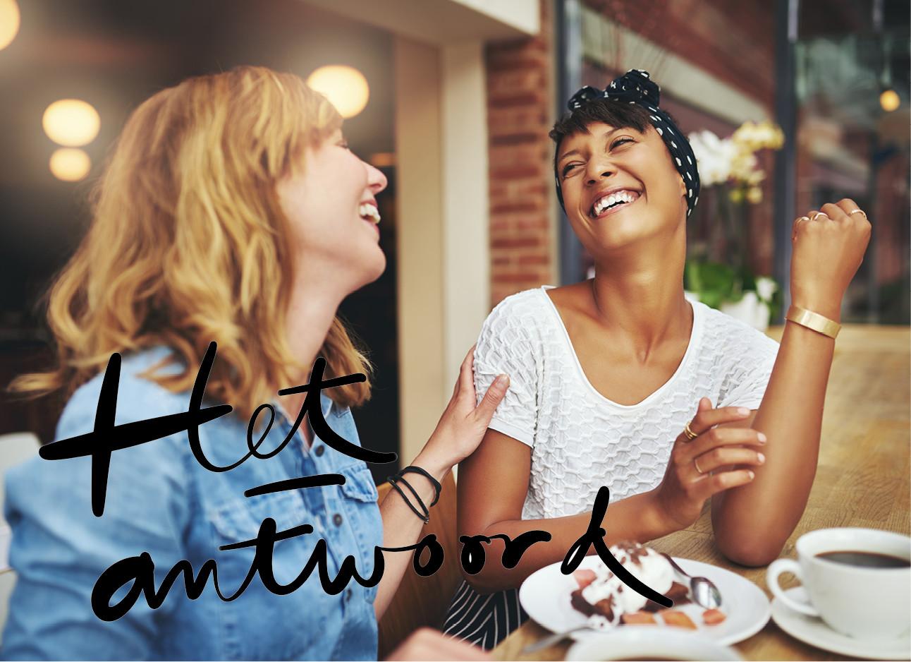 2 meiden die achter een tafel zitten en lachen naar elkaar