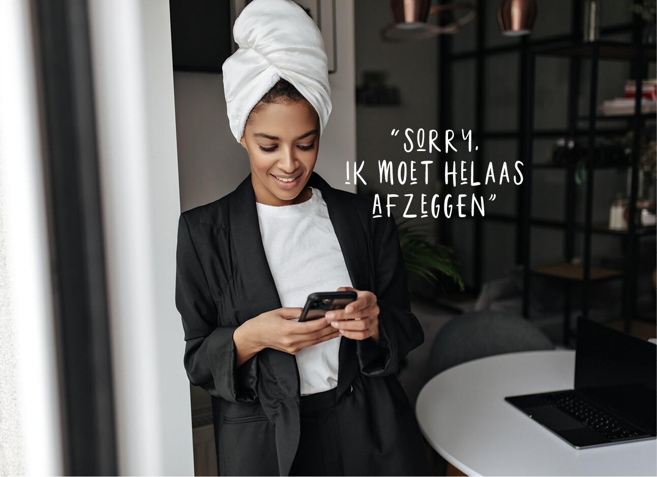 vrouw achter haar telefoon met handdoek op haar hoofd