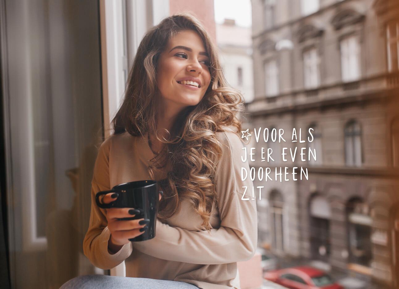 vrouw lachend buiten met een kop koffie