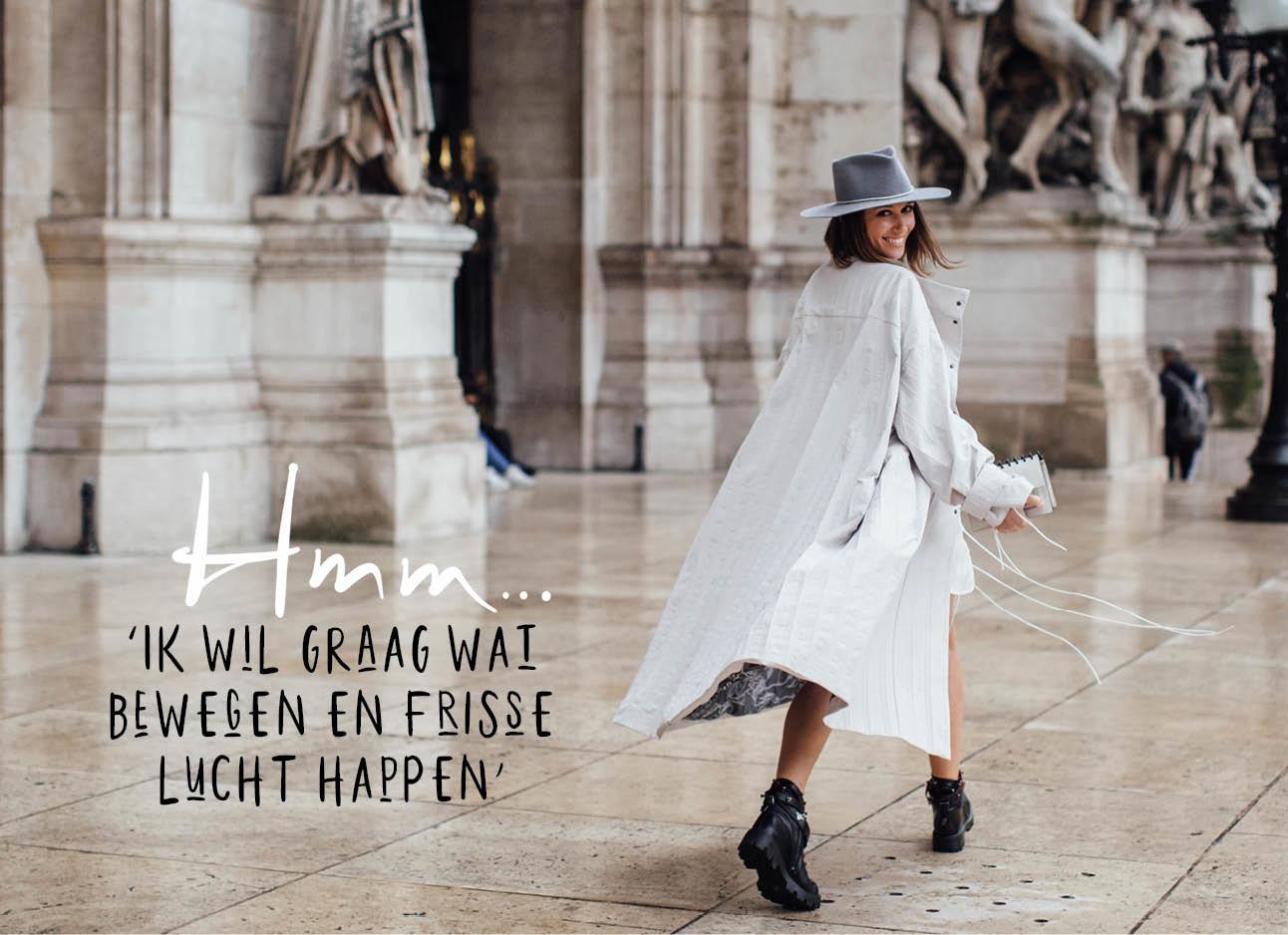 vrouw lopend op straat met een witte lange jas aan het boots met een hoedje