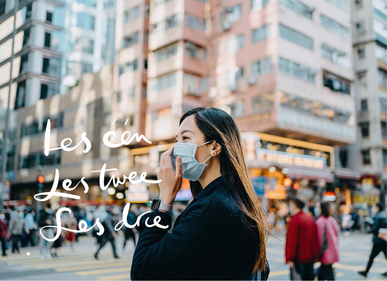 vrouw met mondkapje op straat lopend