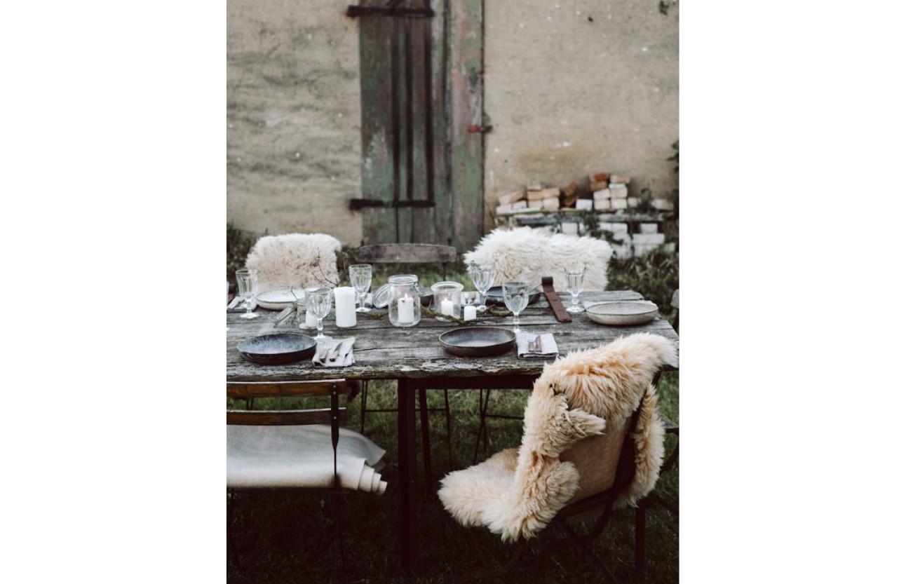 een robuuste tafel met daarom heen stoelen met een wit vachtje erop