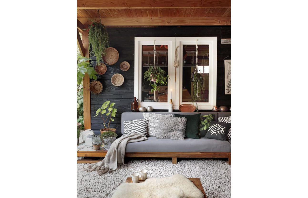 een grijze bank met kussentjes erop en grote witte ramen