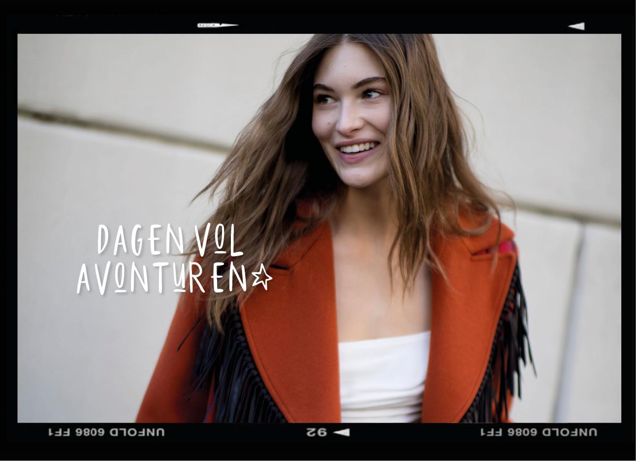 Model op straat lachend met haar haren in de wind