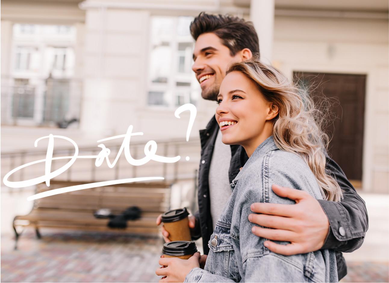 man en vrouw lachend op straat samen arm om haar heen met coffee to go
