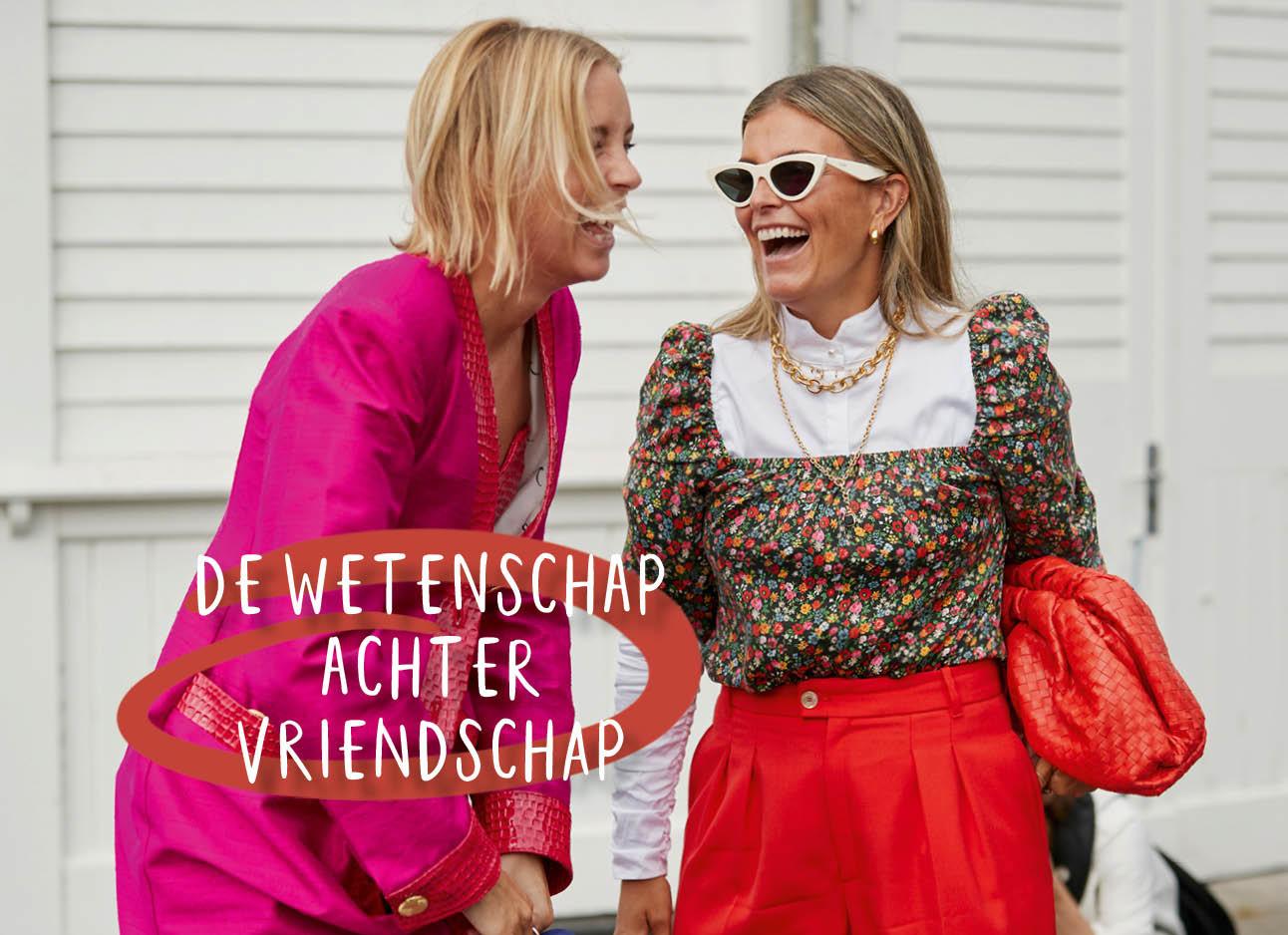 Op de foto staan 2 lachende meiden voor een witte muur