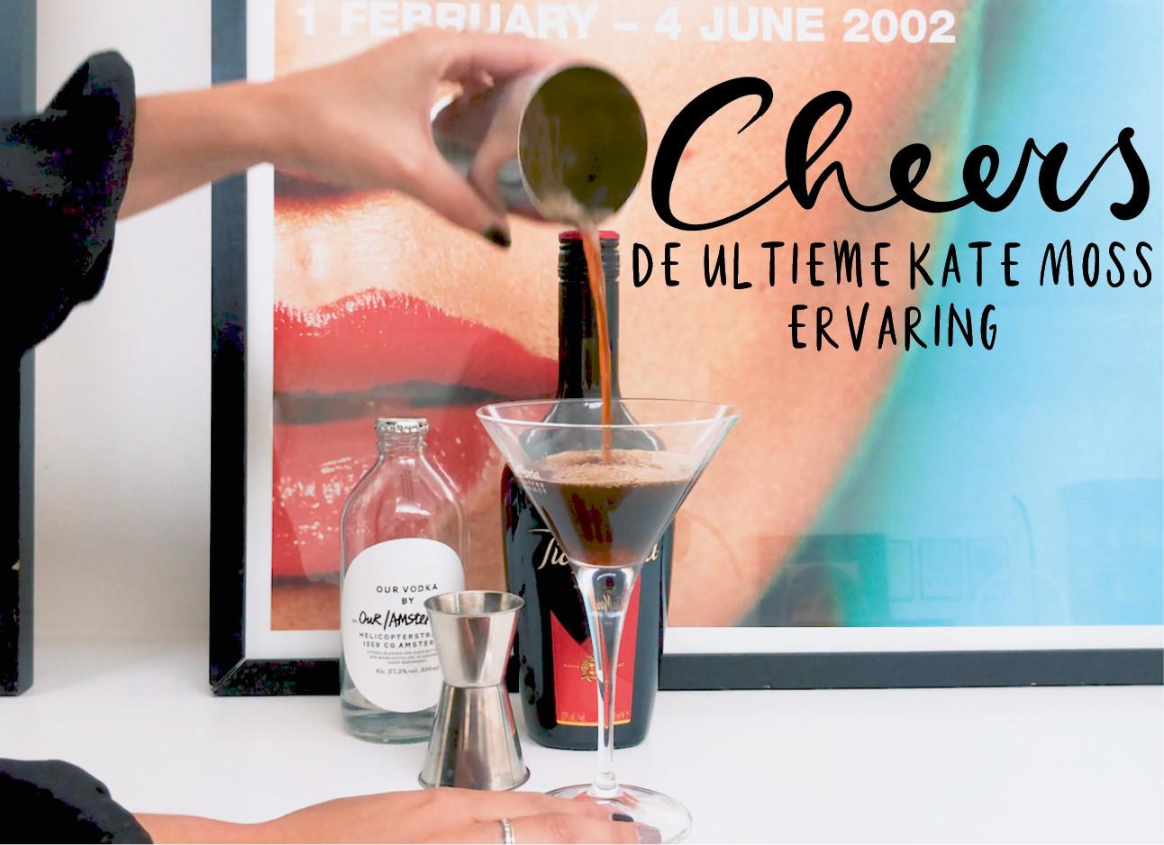 een glas met drinken voor een gekleurd schilderij met een arm die een zwarte trui draagt