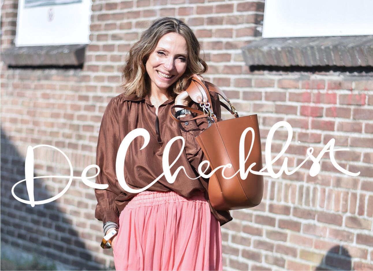 may lachend met haar wandler tas buiten in roze rok en zijde top