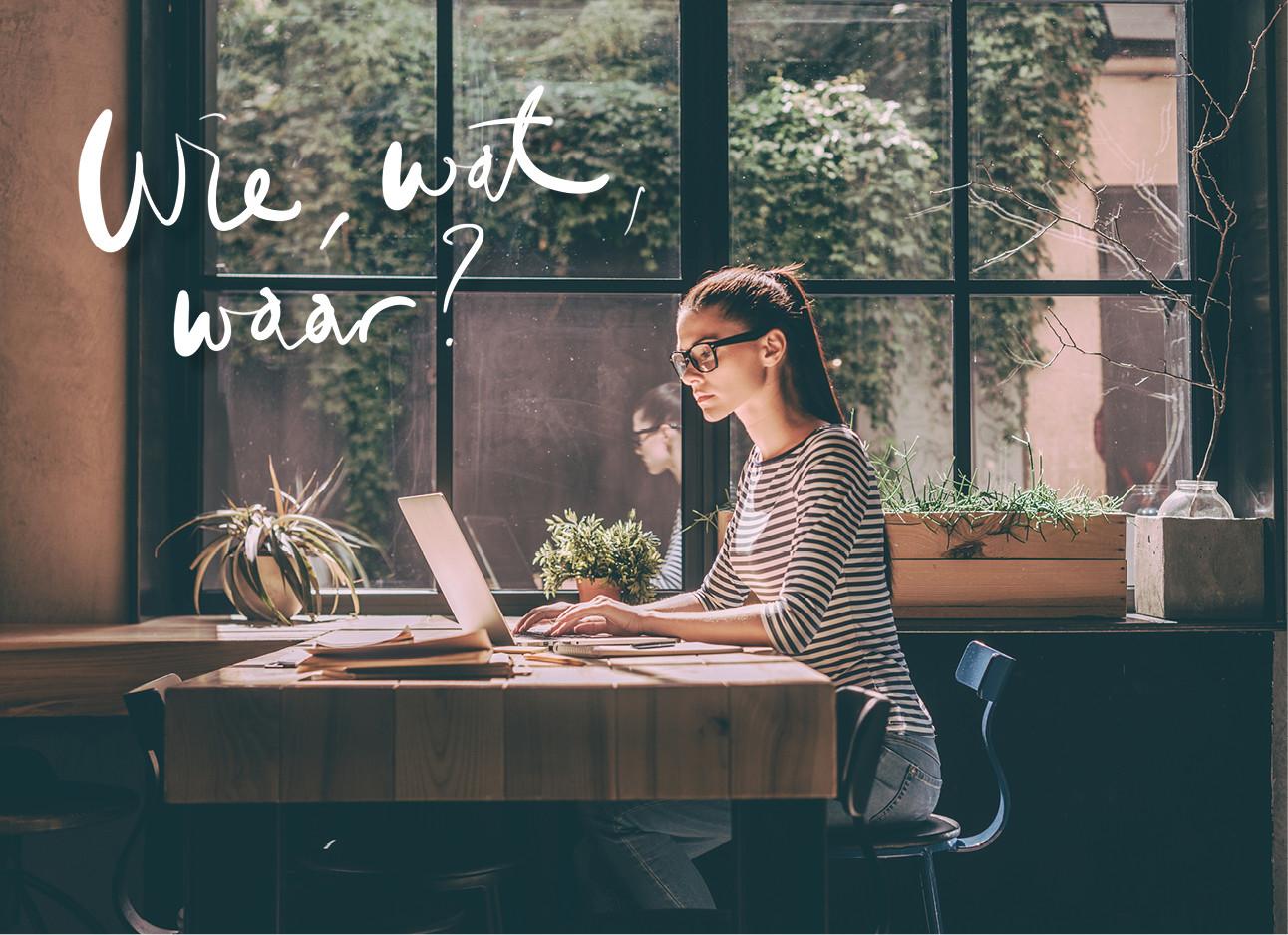 een meisje dat in een cafe achter een laptop zit te werken