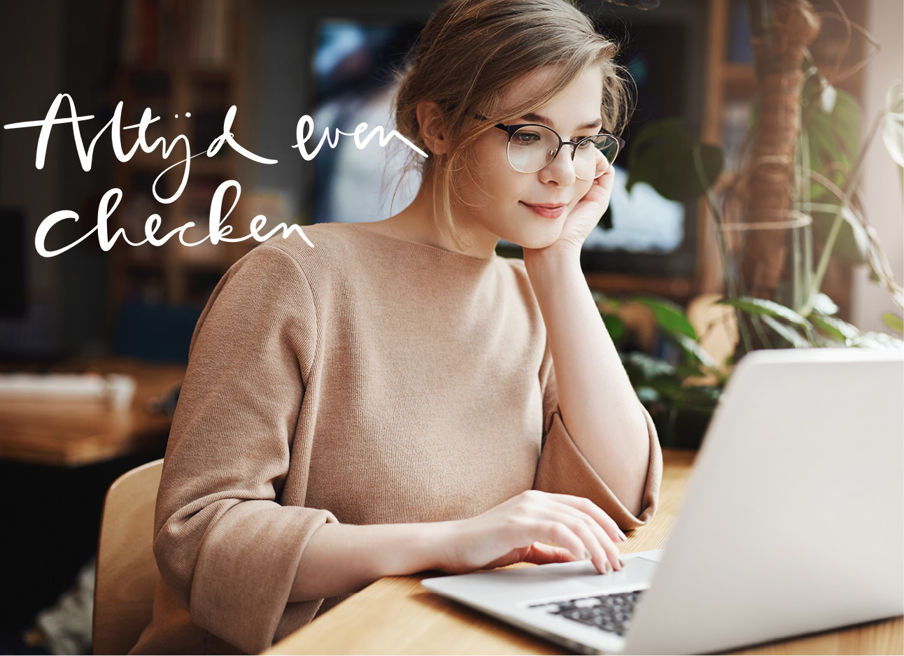 een meisje dat achter haar laptop zit en op haar arm steunt