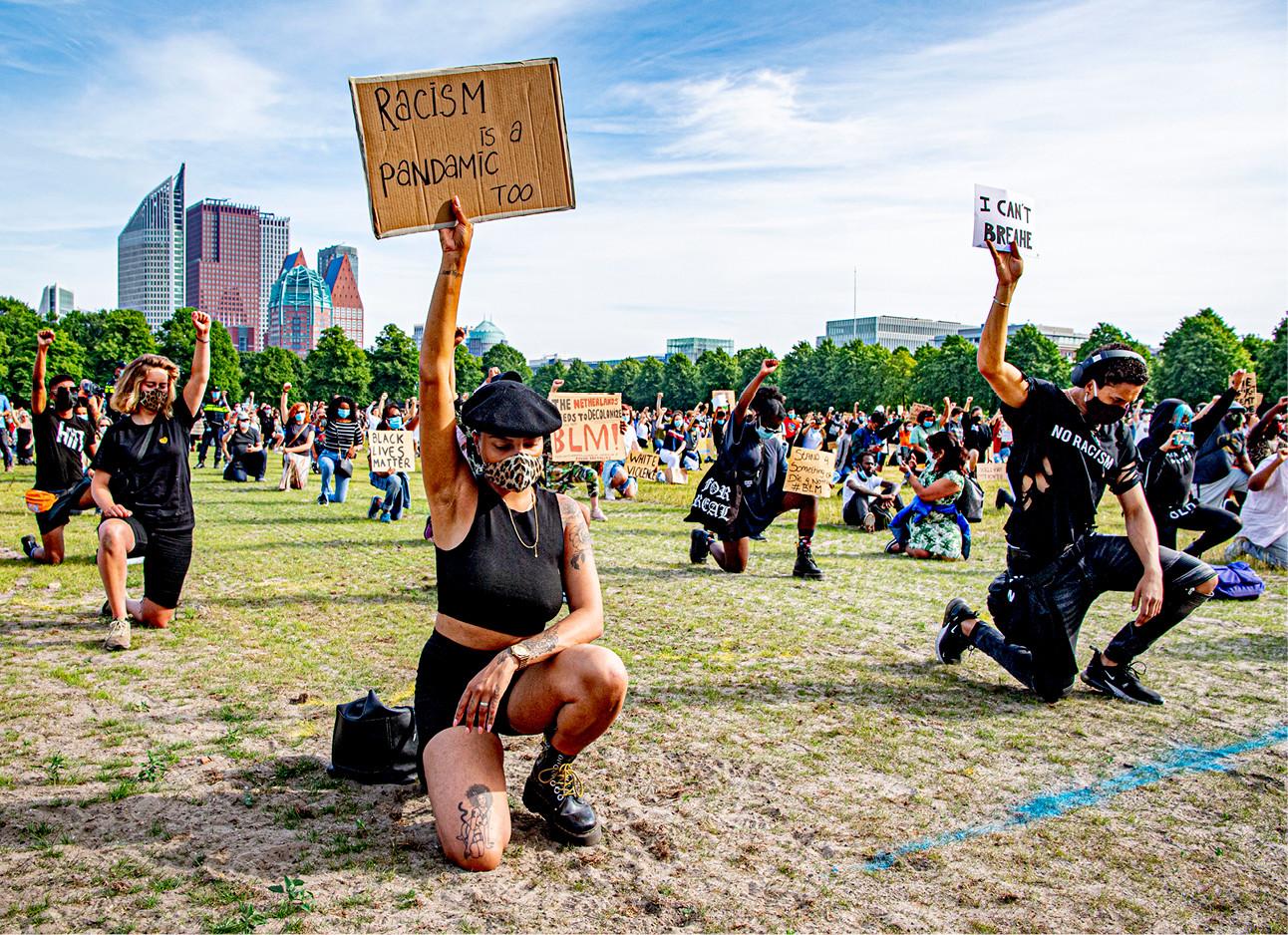 protest den haag, vrouwen en mannen op hun knieeen met protest borden racisme