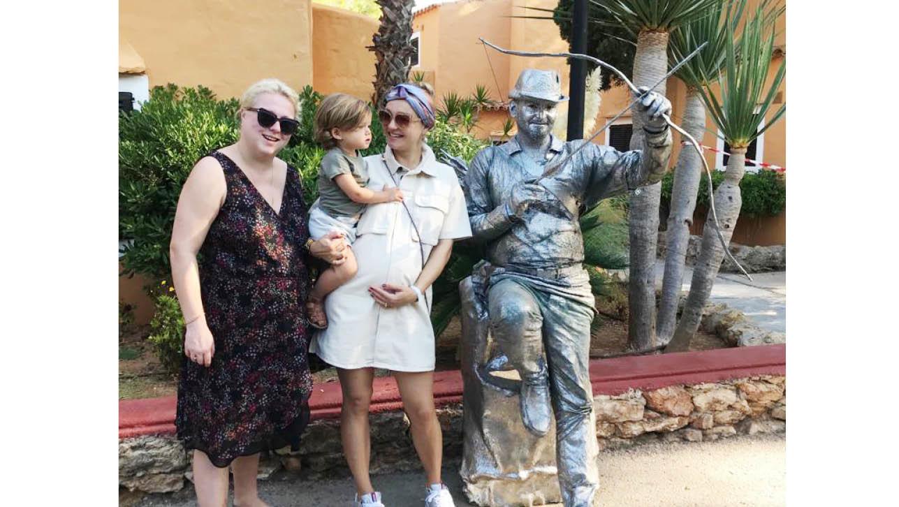 Carolien met haar zus en haar zoontje naast een zilveren beeld