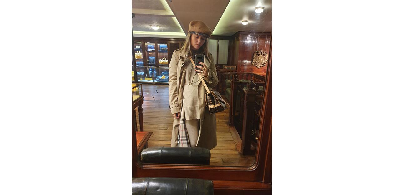 een beeld van carolien die een beige lange jas draagt