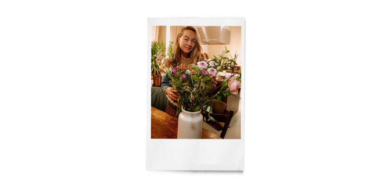 beeld van carolien en een bos bloemen dei ze aan het schikken is