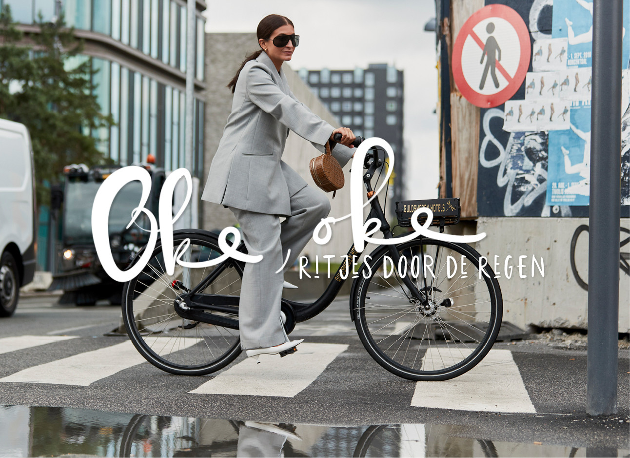vrouw op de fiets door de regen in een grijs pak met een grote grijze zonnebril