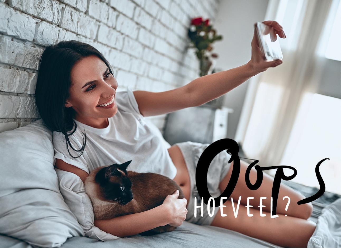 vrouw ligt in bed met haar kat en maakt een selfie met haar telefoon