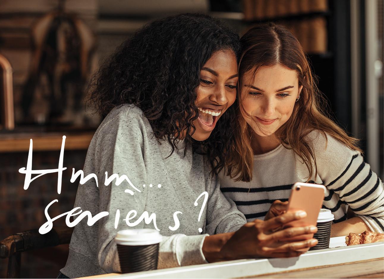 2 meiden die lachend in een cafe zitten en naar hun mobiel kijekn