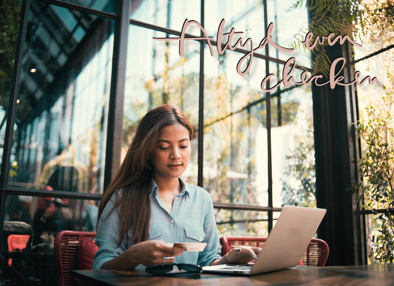 Vrouw zit in een restaurant en kijkt op haar bankpas