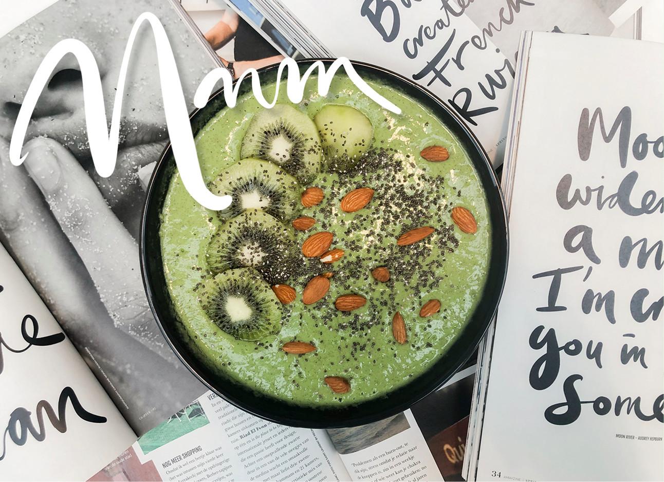 een schaal vol met groene smoothie met stukjes KIWI en amandelen