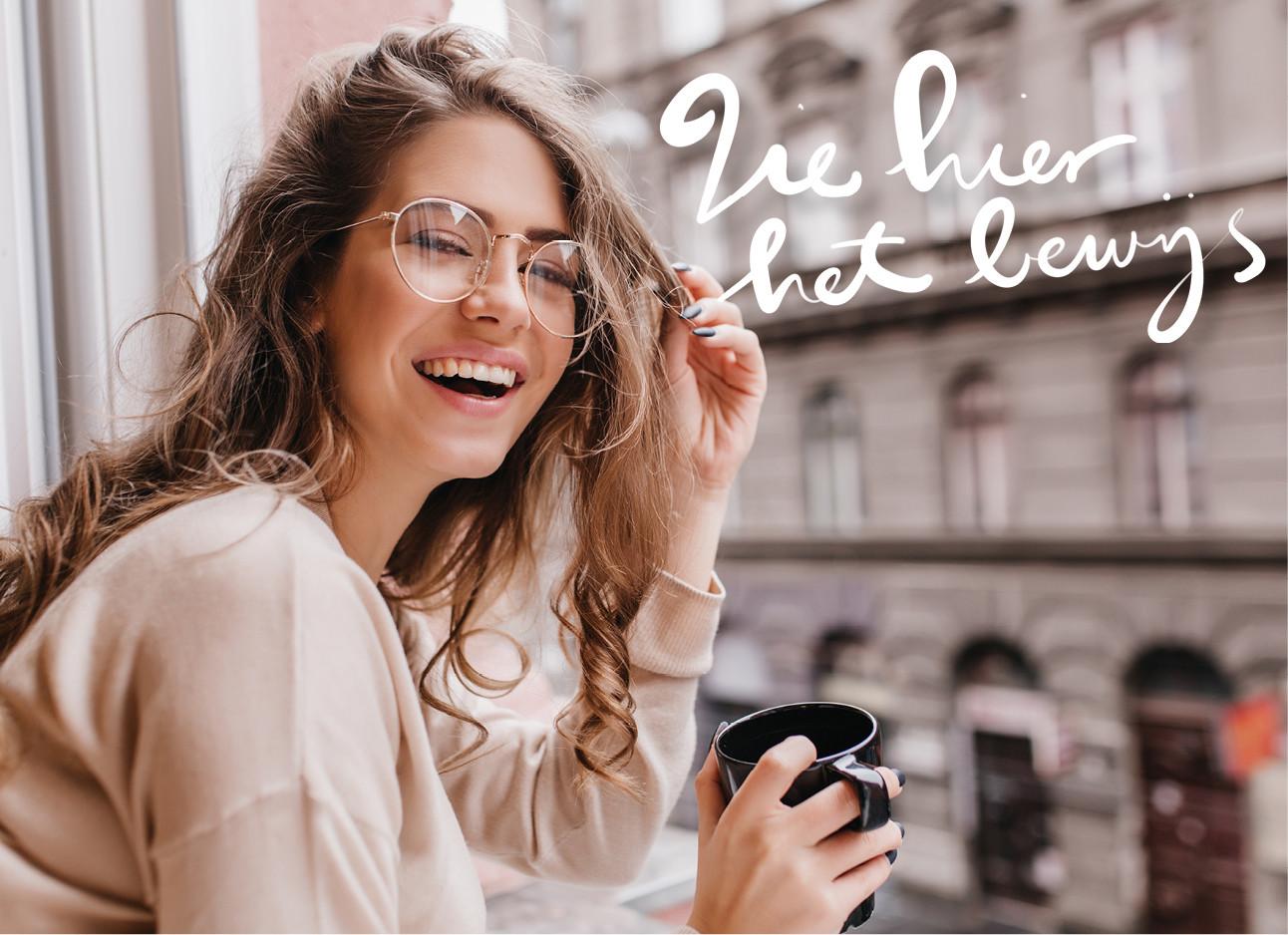 een meisje dat lachend uit een balkon hangt met een kop koffie in der handen