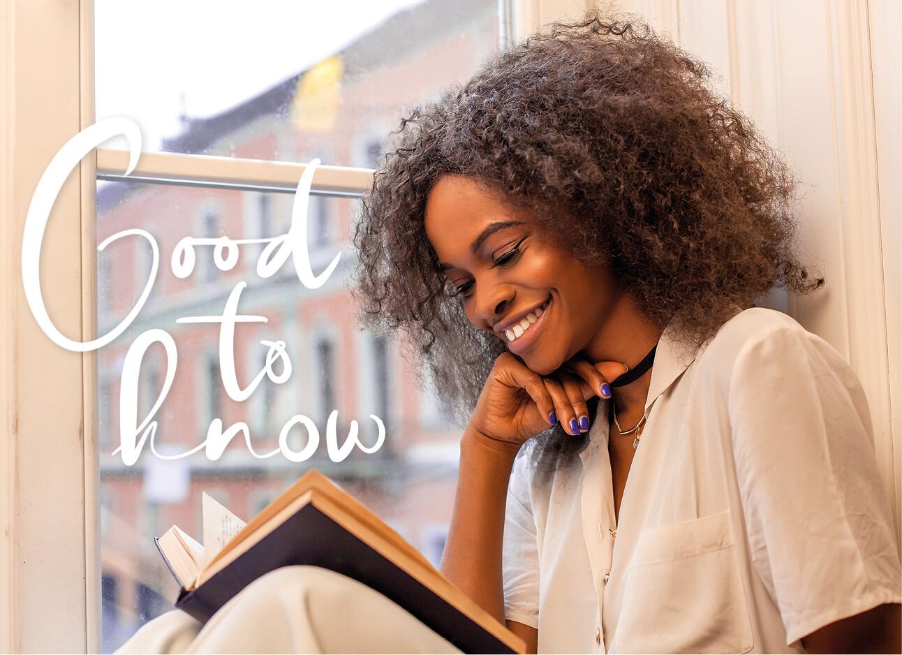 vrouw leest een boekje in haar vensterbank