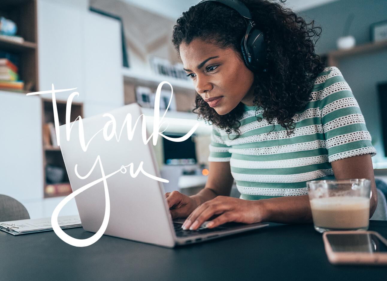 vrouw achter computer met grote koptelefoon