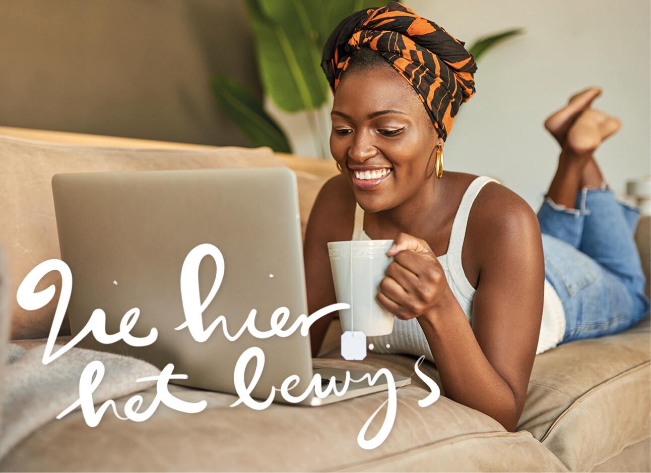 Vrouw drinkt thee achter haar laptop