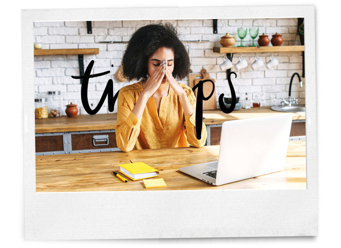 vrouw met handen in het gezicht aan de keukentafel achter haar laptop
