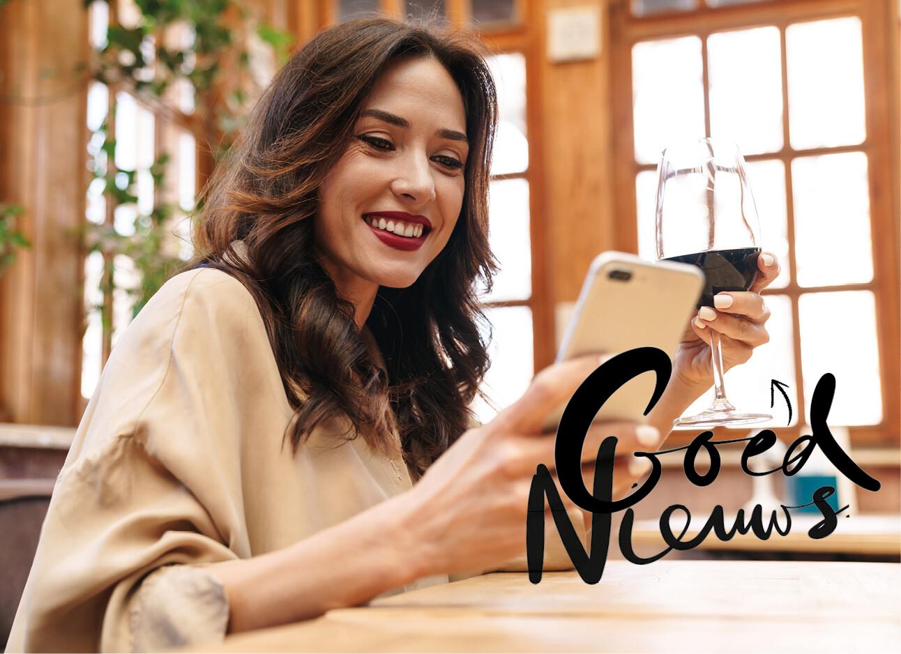 vrouw met rode wijn in hand en kijkend naar telefoon