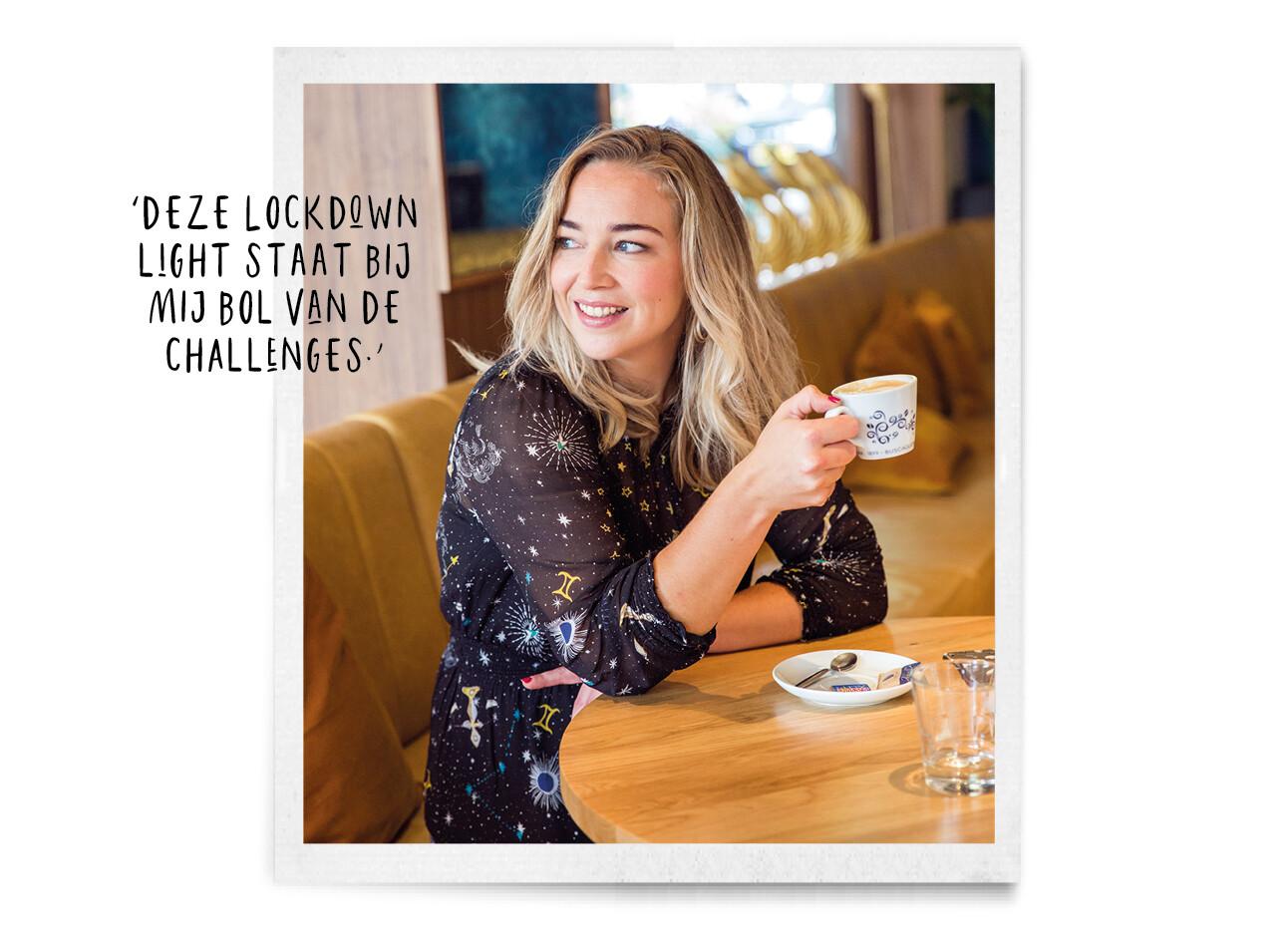Adeline Mans met een cappuccino in haar handen aan een tafel in een restaurant
