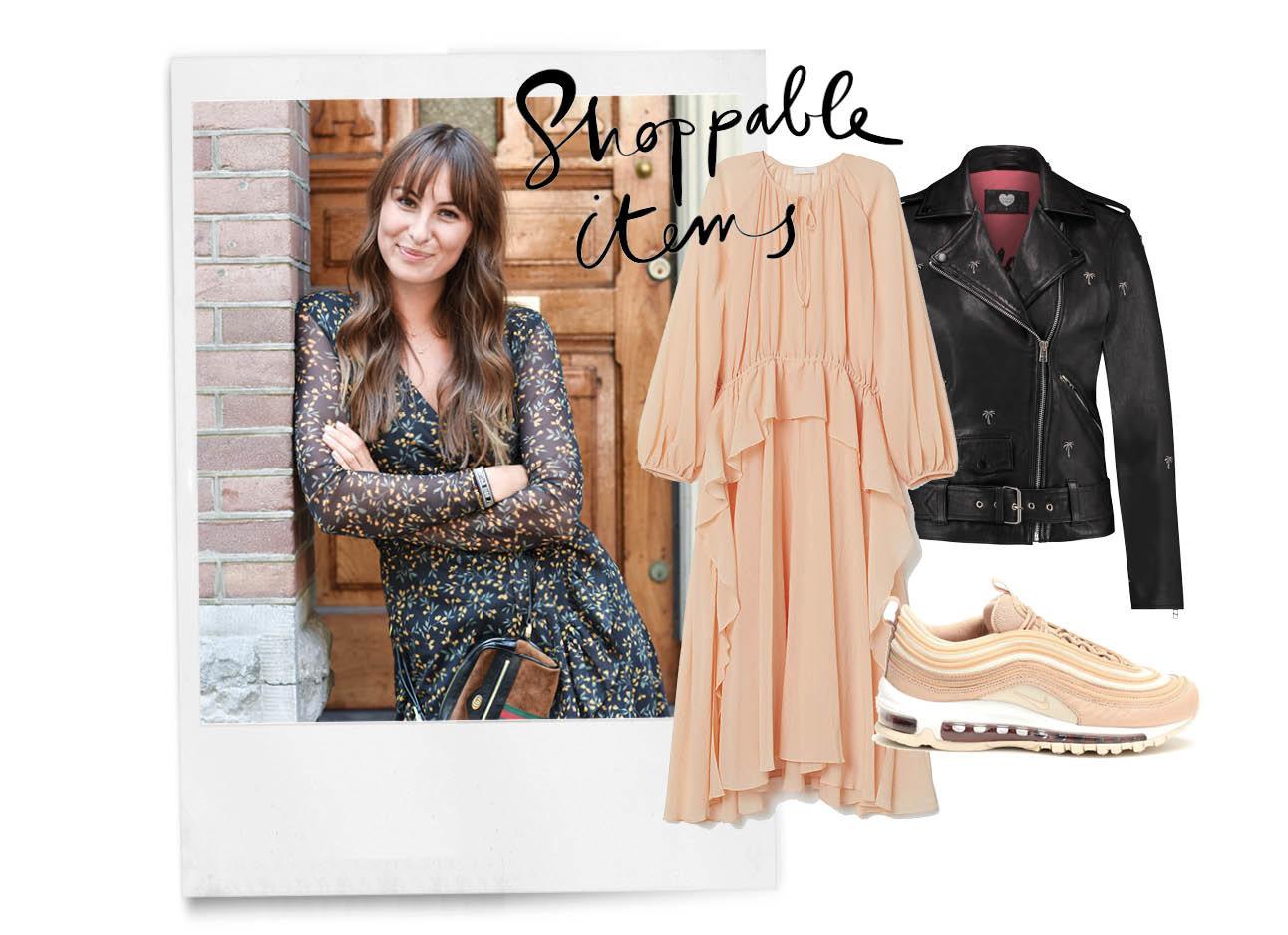 lilian brijl lachend met een zomerse jurk aan en buine gucci jas tegen een amsterdams huis aan met shoping items lange jurk roze zalm en een leer jack en nike gympen