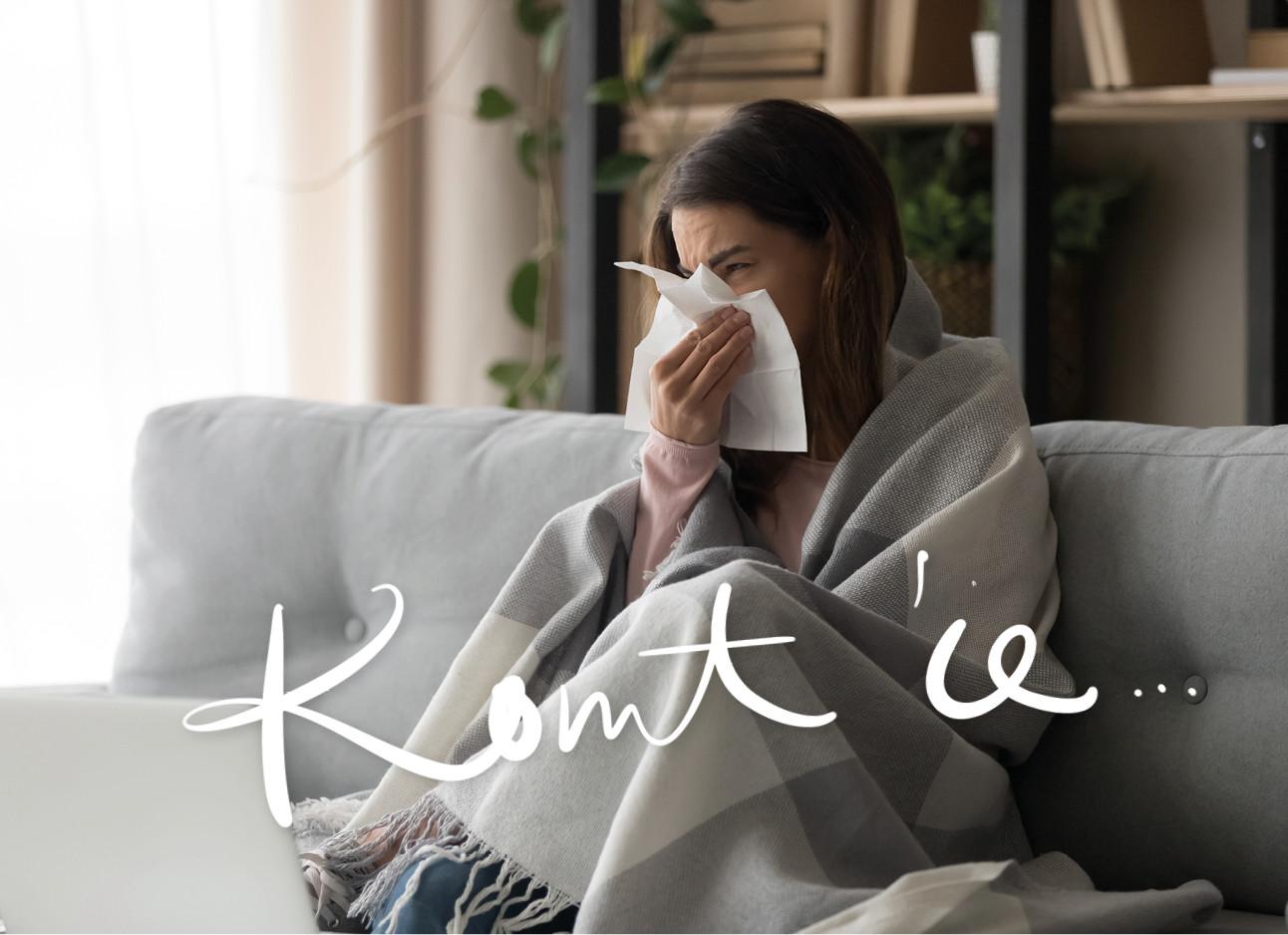 vrouw ziek op de bank aan het snuiten in een servet met een deken over haar heen