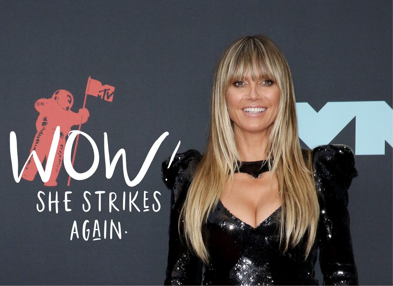 Heidi klum die een zwarte leren jurk draagt en voor een grijze muur staat