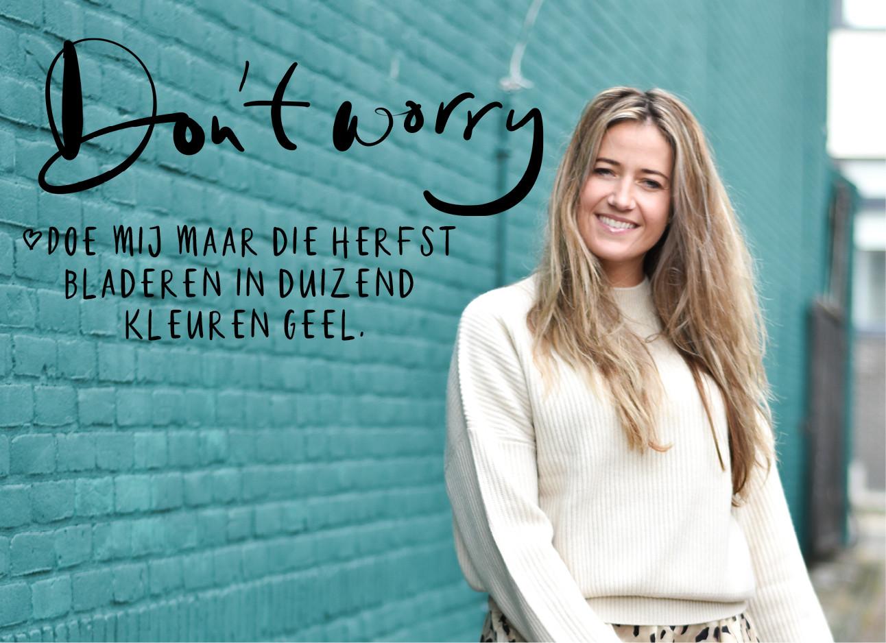 Tessa die een witte trui draagt met een panter rok, ze staat voor een mint blauwe muur