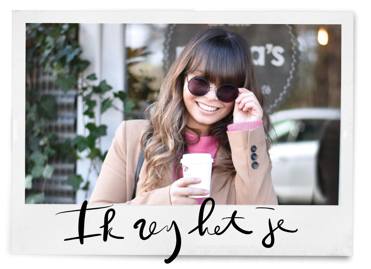 Kiki die met een zonnebril buiten staat en een roze trui draagt